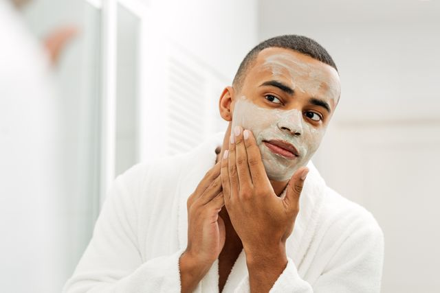 Young Man With Facial Mask Looking In Mirror At Home