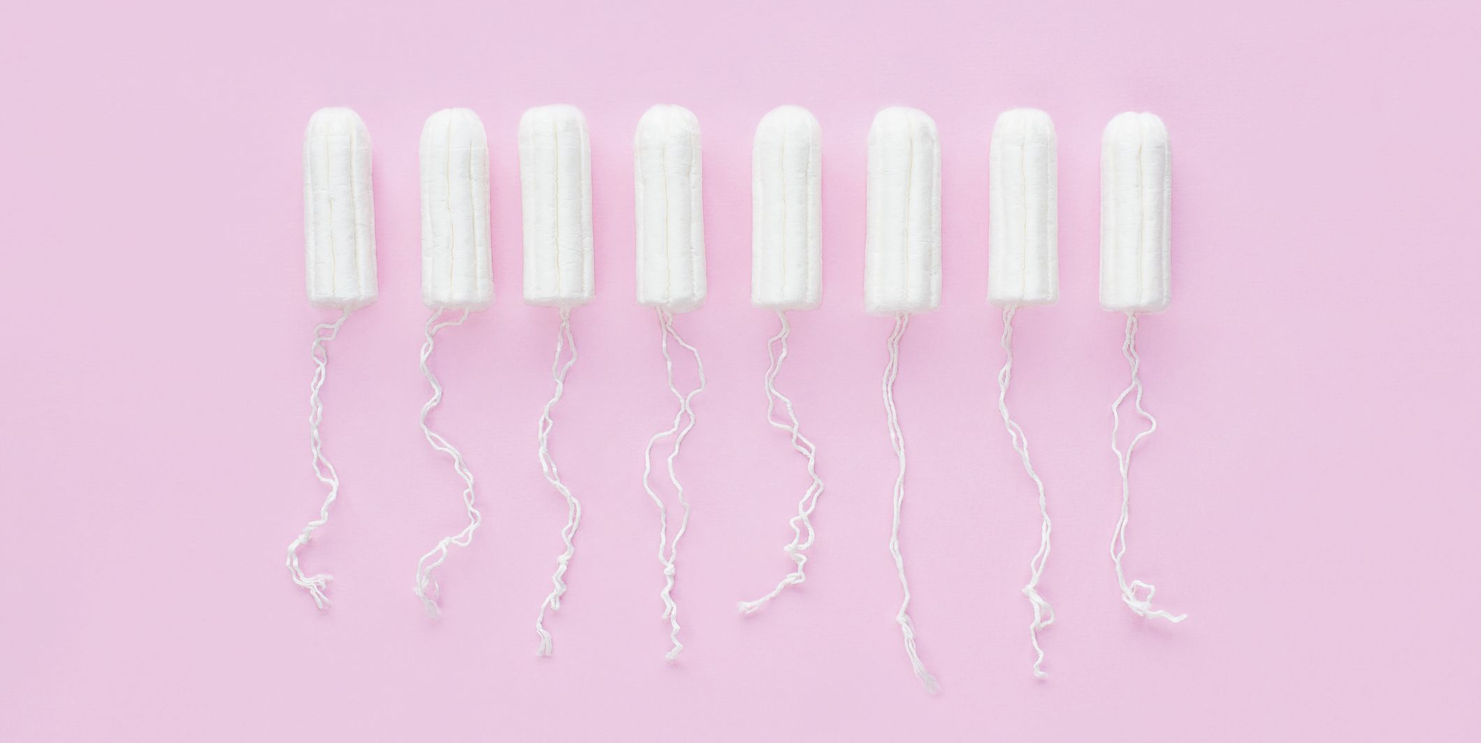 Menstrual period concept. Woman hygiene protection. Cotton tampons on pink background. Top view, flat lay.