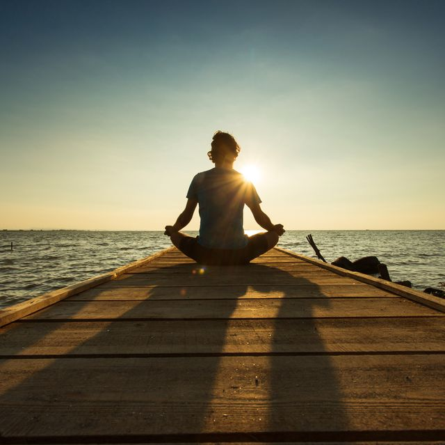 young man sitting and meditating on a pontoon by a lake at the sunrise