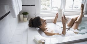 Woman reading book in bubble bath