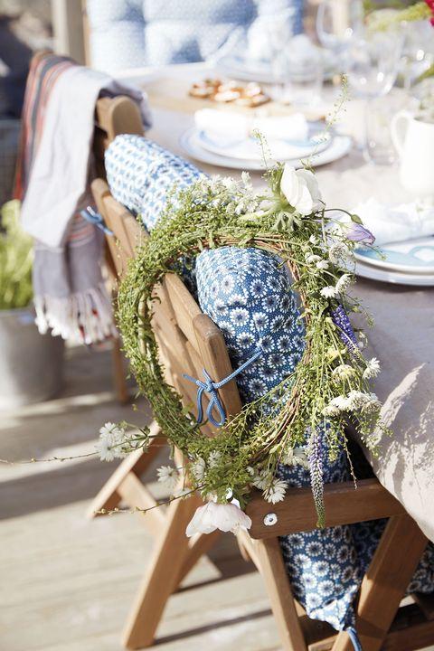 mesa de verano con sillas de madera decoradas con flores