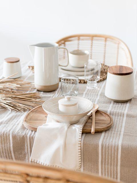 Mesa de comedor decorada en tonos neutros con accesorios de madera