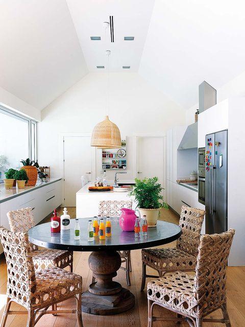 cocina con mesa redonda y sillas de fibras