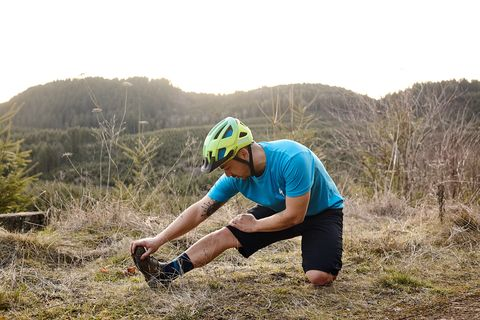 a mountain biker stretching his leg on the trail