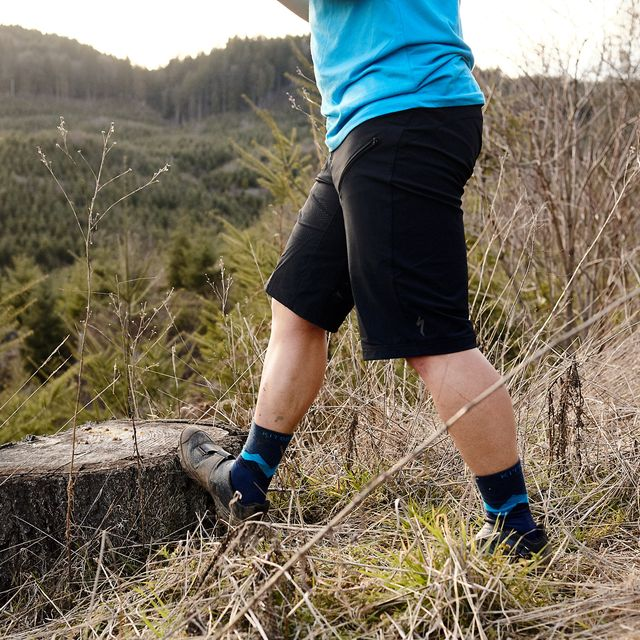 a mountain biker stretching his calf on the trail