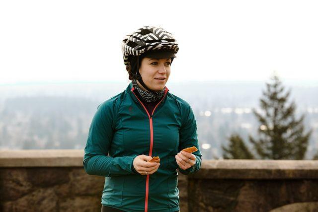 female cyclist eating an energy bar during a ride