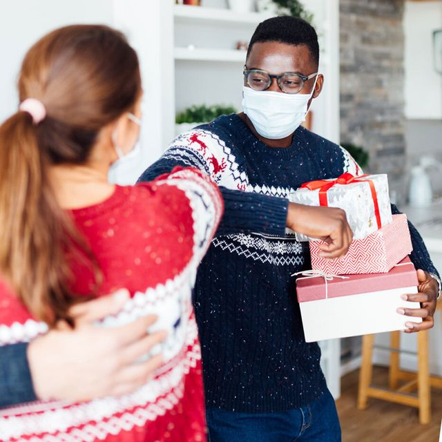 couple elbow bumping while holding presents man boarding airplane with mask on