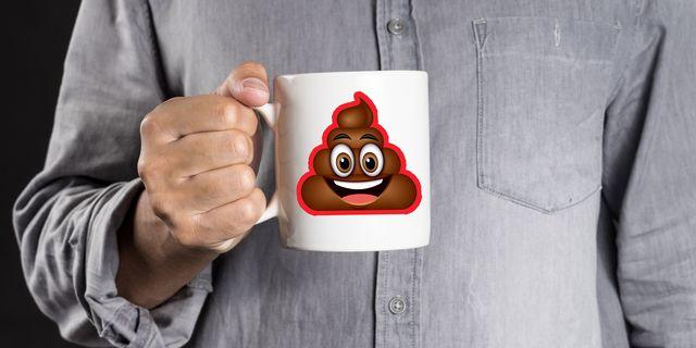 man holding mug with poop emoji on the front