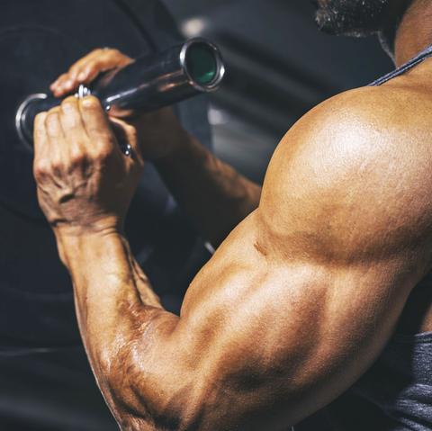 Bodybuilder preparing a barbell on a power rack in gym