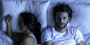 Man lying awake in bed next to sleeping wife
