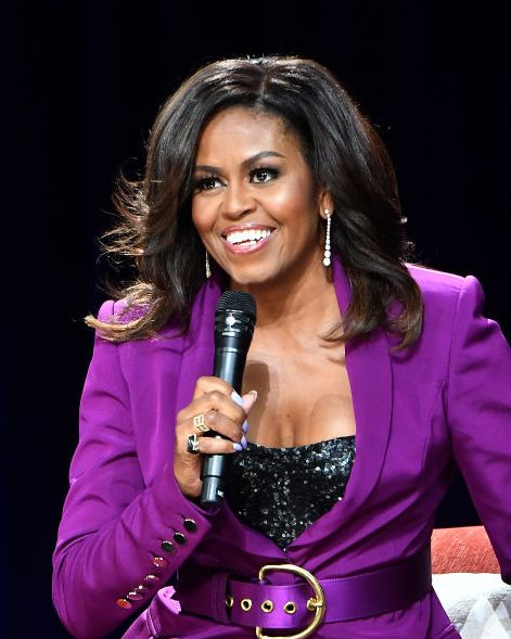 former first lady michelle obama wears a purple suit and holds a microphone