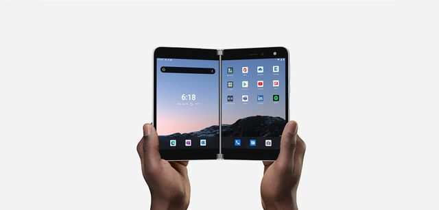 two hands holding microsoft's folding surface duo phone open like a book
