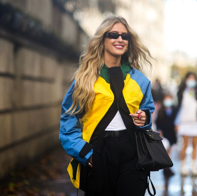 paris, france   october 05 emili sindlev wears sunglasses, a white t shirt, a blue  green  yellow long rain coat, a black leather kelly handbag form hermes, high waist black large pants, a red nailed  studded ring, outside lacoste, during paris fashion week   womenswear spring summer 2022, on october 05, 2021 in paris, france photo by edward berthelotgetty images
