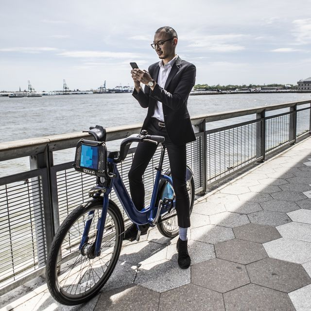 mid adult businessman on bicycle looking at smartphone along city river waterfront