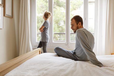 Mid adult couple in bedroom, having disagreement