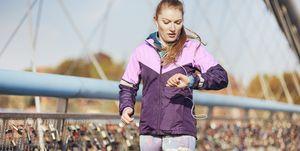 Mid adult female runner checking time whilst running across bridge