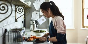 Mid adult Korean woman chopping vegetables on kitchen counter