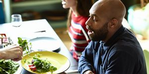 Mid adult man at dinner party holding plate and being served salad