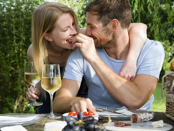 mid adult man feeding girlfriend from picnic table in garden