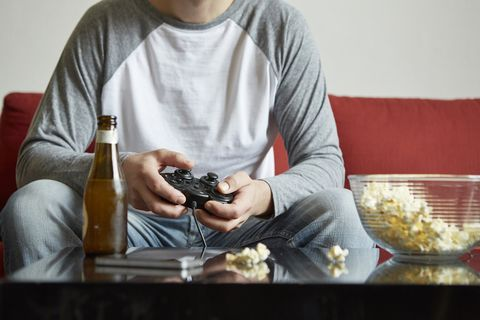 Mid adult man sitting on sofa using computer game control