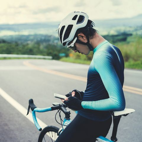 Mid Adult Man Using Phone Sitting On Bicycle At Road