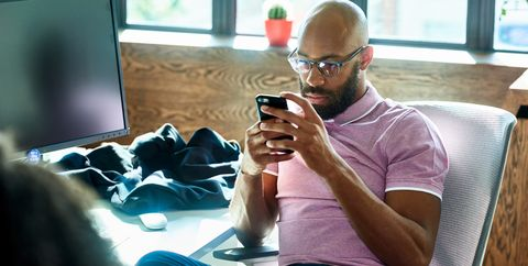 Mid adult man with beard and glasses texting in office