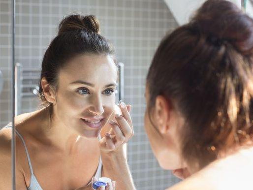 Mid adult woman applying contact lens in bathroom mirror.