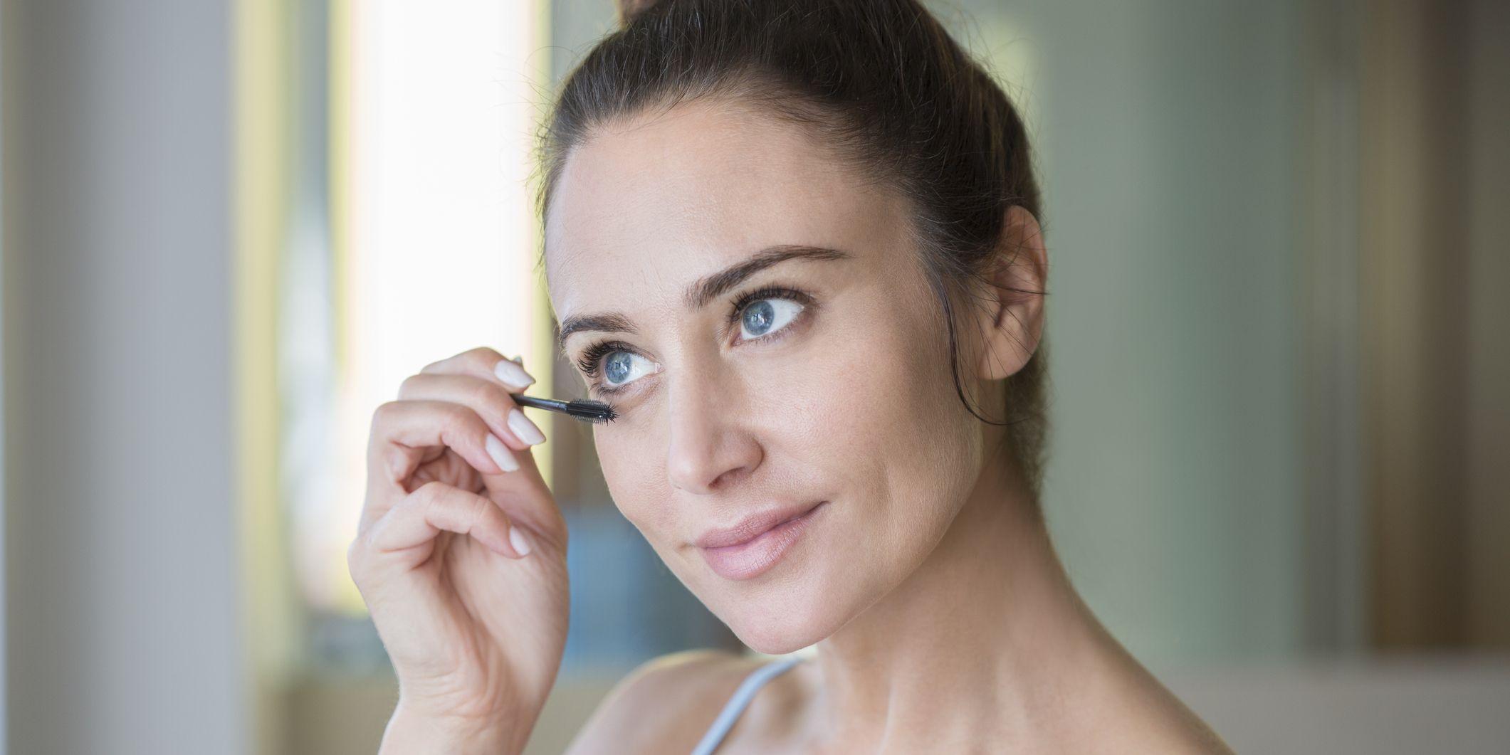 Mid adult woman applying mascara.