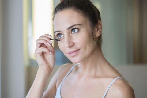 mid adult woman applying mascara