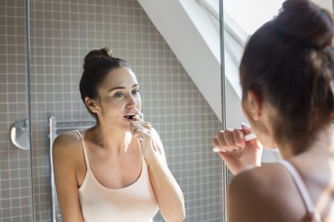 mid adult woman brushing teeth in bathroom mirror