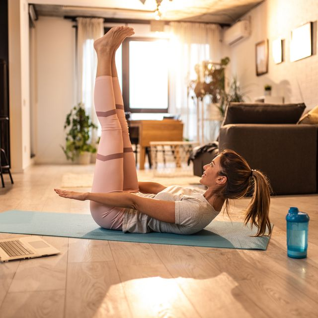 mid adult woman doing yoga at home