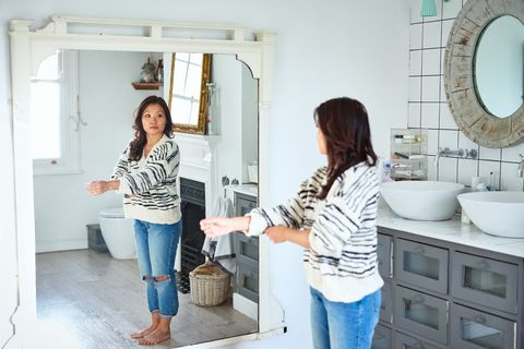 Mid adult woman getting dressed and looking in mirror