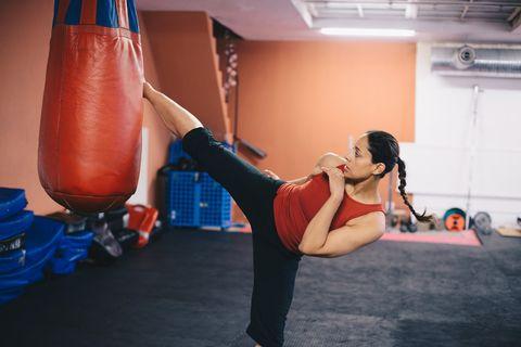 Mid adult woman kicking punching bag at gym
