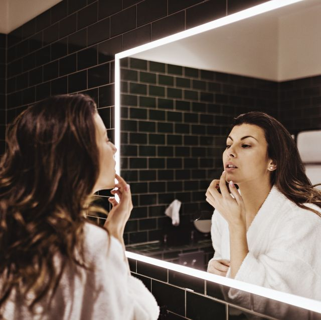 mid adult woman looking in mirror while applying lip balm
