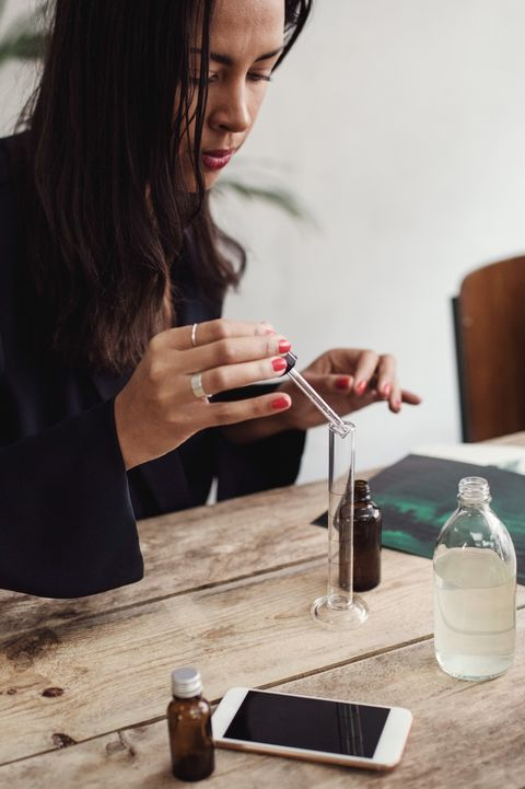 Mid adult woman mixing liquid with pipette in test tube at table in perfume workshop
