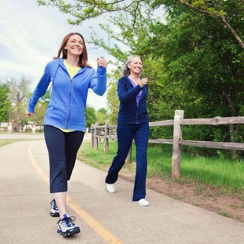 mid adult woman passes senior woman during power walk
