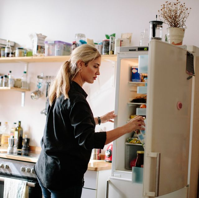 mid adult woman removing milk carton from refrigerator in kitchen at home