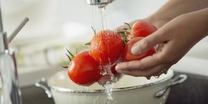 Mid-adult woman rinsing tomatoes in sink with colander.
