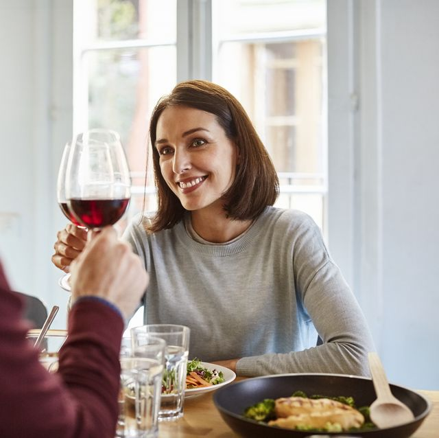 mid adult woman toasting wine glass with man