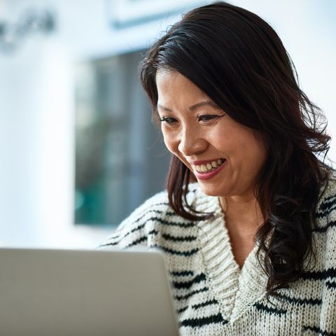 mid adult woman using laptop and smiling