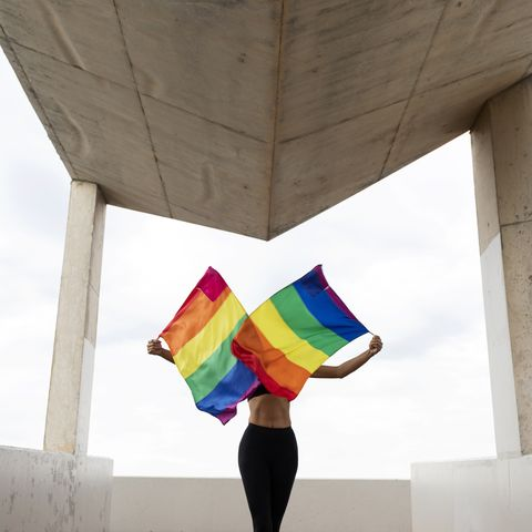 mid adult woman waving rainbow flags while standing on built structure against sky