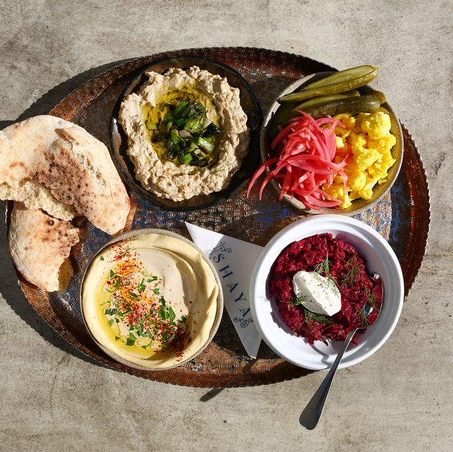 a maza platter with hummus, baba ganoush and pita bread along with pickled vegetables