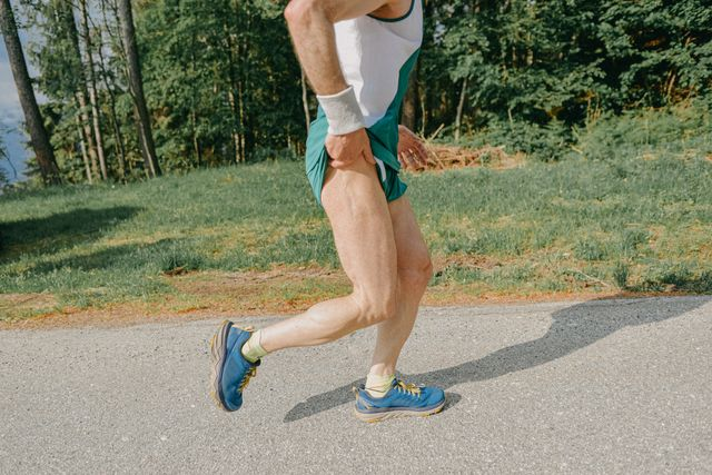 middle age man running on the side of a asphalted mountain road