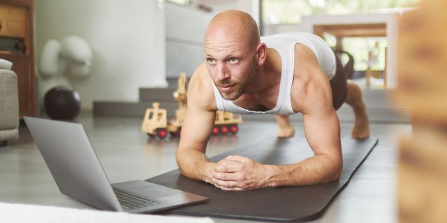 a middle aged man is exercising at home with the help of a laptop and doing fitness exercises, pushups, situps and other sporting activities on a fitness mat