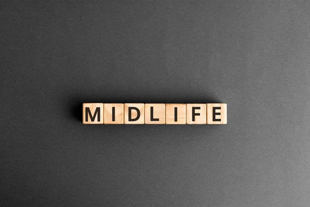 midlife   word from wooden blocks with letters, middle age midlife concept,  top view on grey background