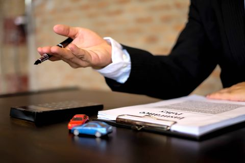 Midsection Of Agent With Insurance Papers On Table Sitting In Office