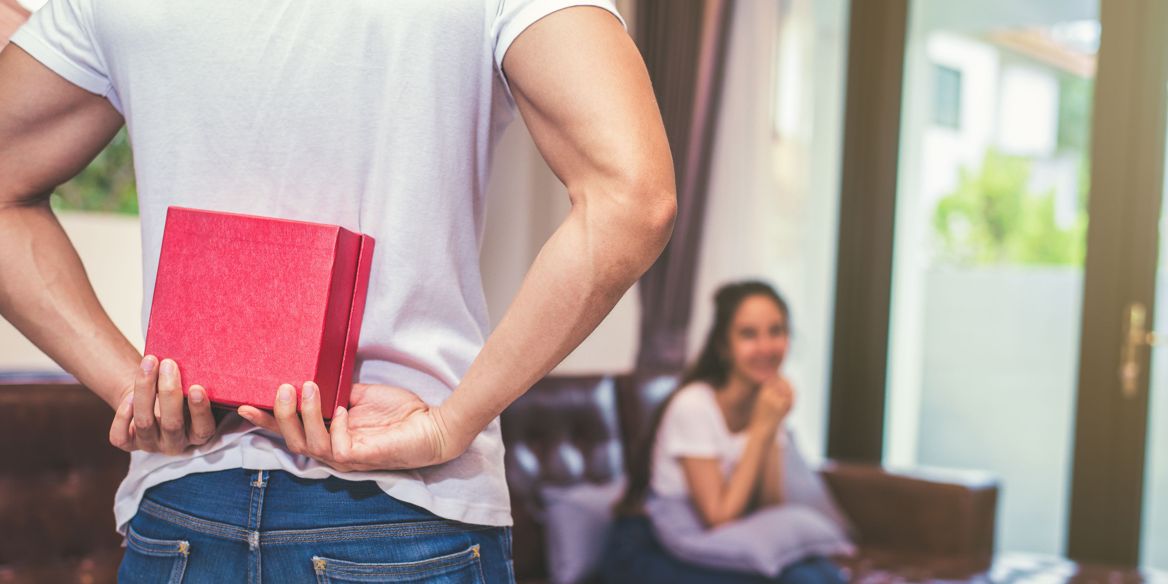 Midsection Of Boyfriend Hiding Gift While Girlfriend Sitting On Sofa At Home