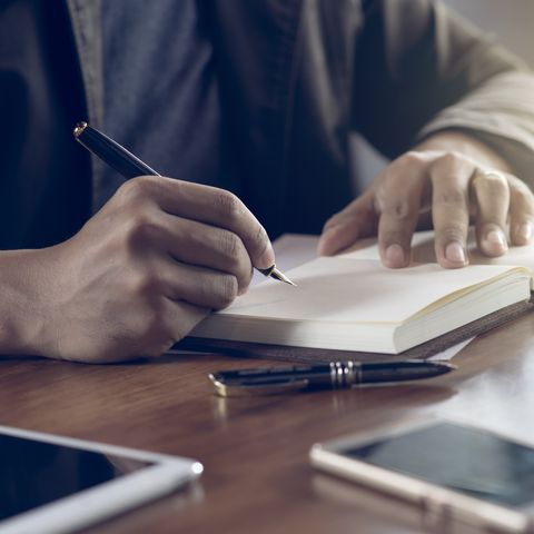 Midsection Of Businessman Writing In Book On Table