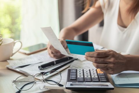 midsection of businesswoman holding credit card and bill while working at desk