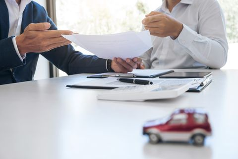 Midsection Of Car Insurance Agent Giving Document To Customer